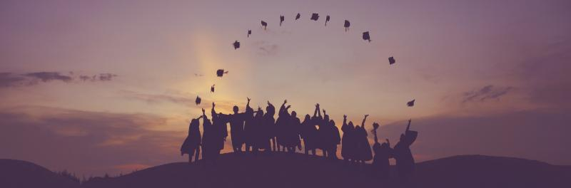 Image of students throwing graduation caps in air at dusk