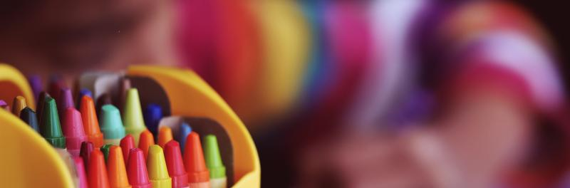 Child wearing colored stripes with box of crayons in foreground