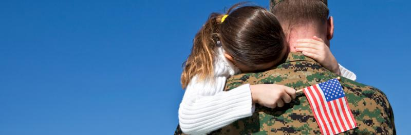 Child hugging solider
