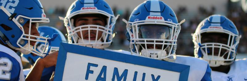 "football players holding a sign the says ""family"""