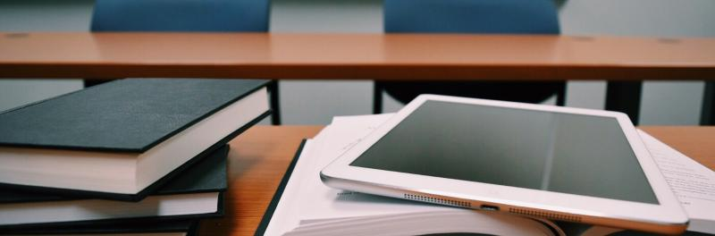 Closeup of textbooks and electronic tablet sitting on desk
