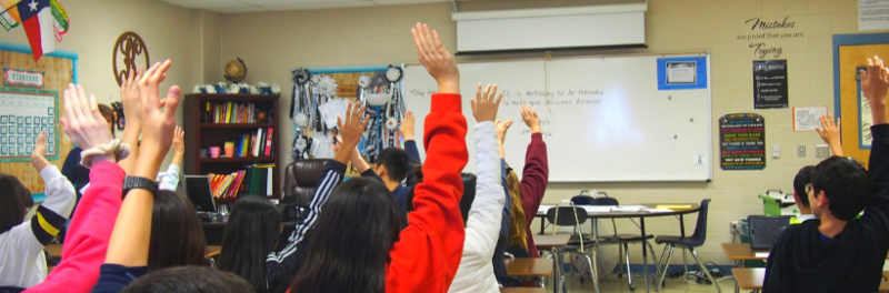 Students in Classroom Raising Their Hands