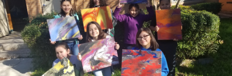 Students involved in Art Club holding their acrylic pour paintings in the lawn.