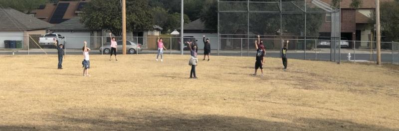 students outside in the field playing tag.