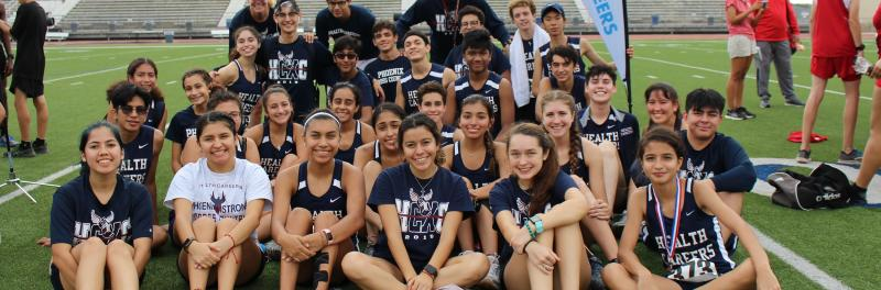 group photo of the cross country team and their coaches on the track field