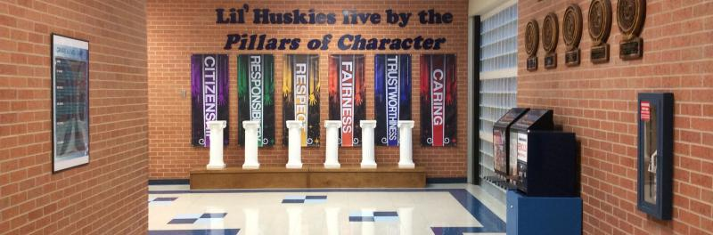 White columns displaying the Lil' Huskies live by the Pillars of Character.