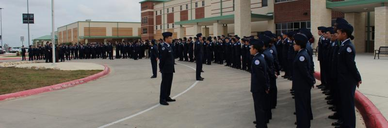 JROTC standing in attention outside the campus.