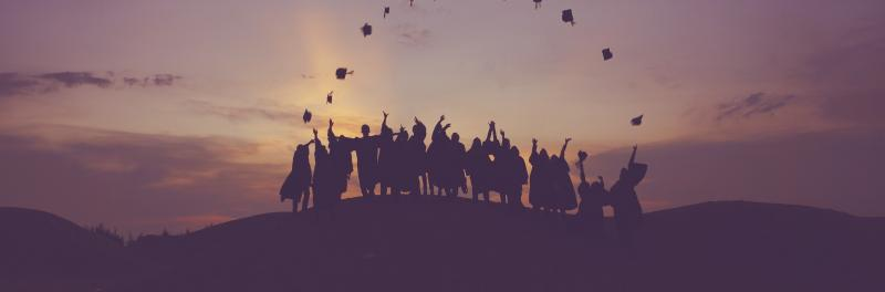 Silhouette image of a group of students in the distance wearing graduation gowns tossing their caps in the air.