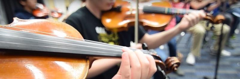 A group of students playing instruments in orchestra
