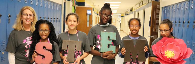 Teacher and 5 girls standing in a school hallway handing letters to spell STEM.
