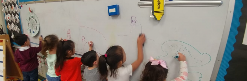 Kids drawing on the classroom white board