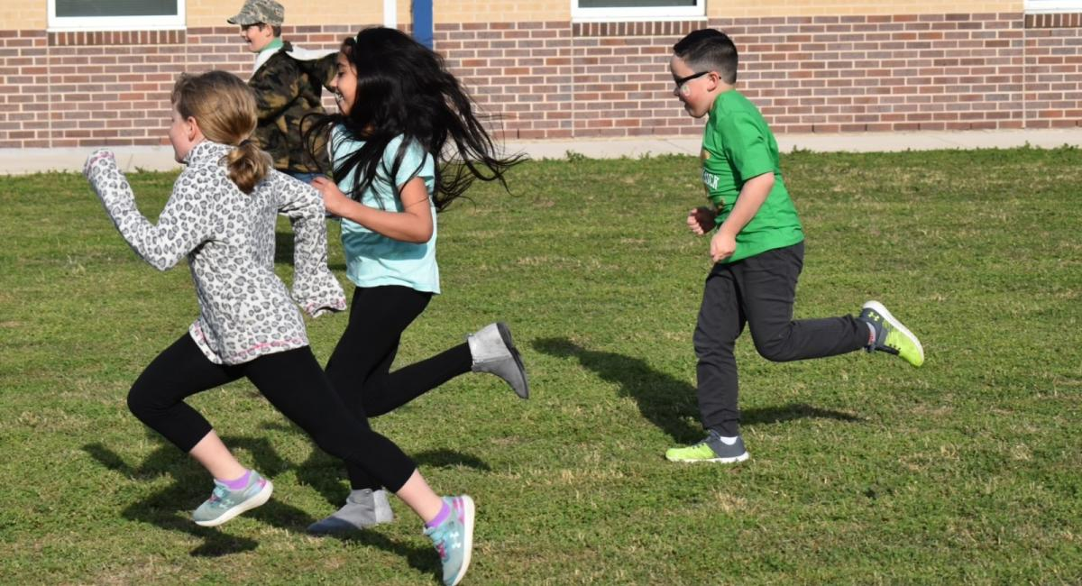 Students running on the green lawn of the Franklin campus during field day.