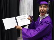 Student holding his diploma at graduation