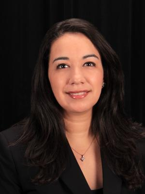 Principal Anabel Romero in front of black background