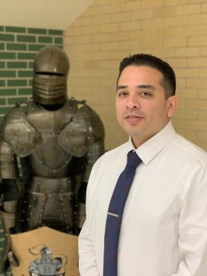 Principal Jose Mendez in front of black knight