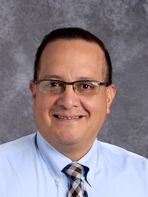 Mr. Alvarez wearing a Blue dress shirt with darker blue tie. Wears glasses and has a smile.