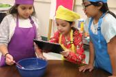 Female student in yellow chef hat uses iPad to take pic of cooking process