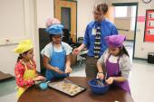 Teacher talking to three female students wearing aprons