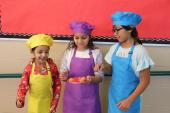 Three girls in chef hats and aprons taste desert on plate