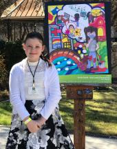Emily poses outside with a picture of her winning artwork on an easel