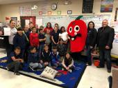 A picture of Mrs. Peralta and her students posing next to Principal Garcia, the red apple NEF mascot and NEF representative