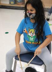 Meadow Village student plays rhythm sticks on her chair in classroom