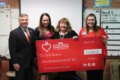 Group of four posing with oversized check for HEB Awards
