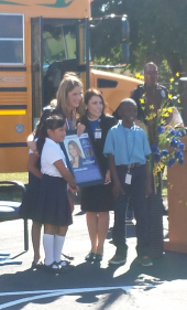Jenna Bush Hager poses with Dr. Arteaga and Passmore students in front of a school bus