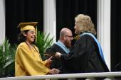 Board President M'Lissa Chumbley hands a diploma and congratulates her mentee Chloe Delgado on her graduation