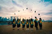 Photo of graduates throwing caps in the air