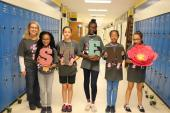 students and teacher posing in hallway with letters spelling STEM